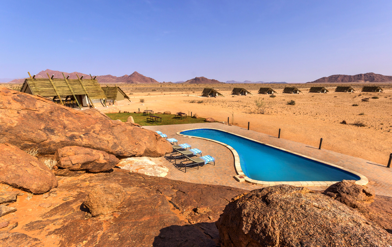 Desert Quiver Camp  - Sossusvlei  Conveniently located a mere 5km from the entrance gate to Sossusvlei, the inspiring scenery characterised by granite outcrops, spectacular views and roaming wildlife will captivate your senses. Add 2 nights to the beginning or end of your retreat.