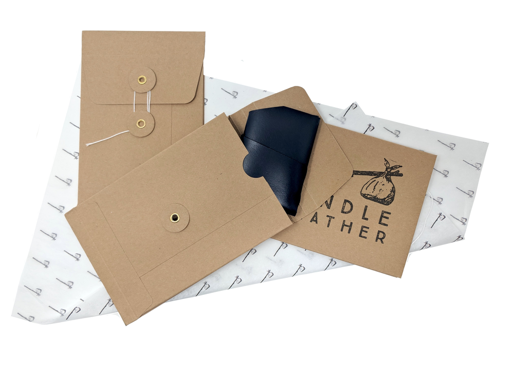A minimal wallet being packaged in Bindle branded envelope and tissue paper