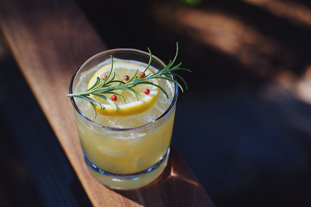 ingredients: - 1 1/2 oz gin1/2 oz spice tea liqueur3/4 oz fresh lemon juice3/4 oz citrus-rosemary syrupGarnish: lemon wheel, rosemary sprig & pink peppercorns.