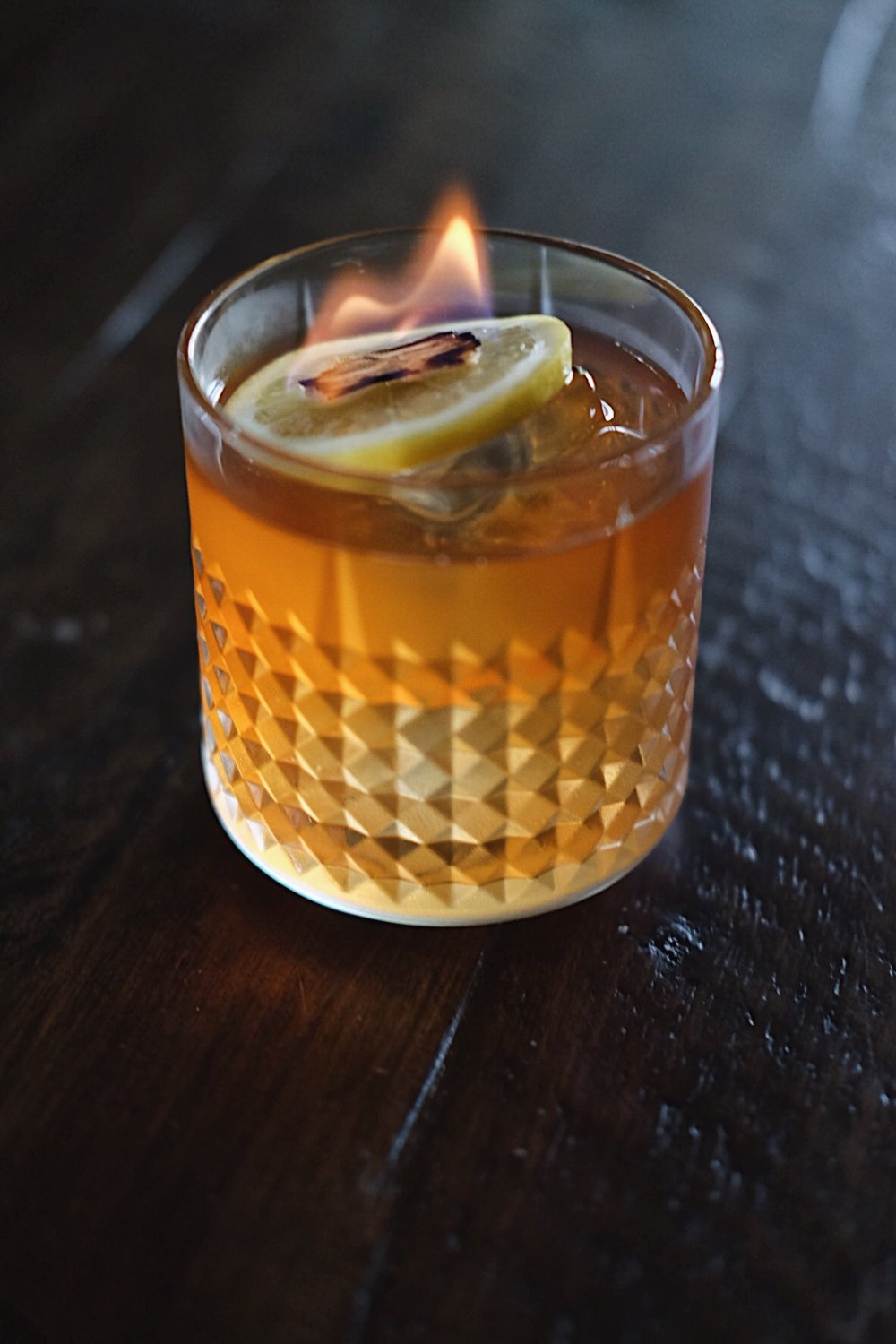 ingredients: - 2 oz blended scotch1/2 oz smoke tea liqueur1/2 oz yellow chartreuse3 dashes Peychaud's bitters2 dashes barrel-aged aromatic bitters1/2 tsp honey syrupGarnish: Lemon wheel & flamed cedar chip