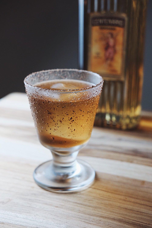 ingredients: - 2 oz reposado tequila3/4 oz Ancho Reyes chili liqueur1/4 oz coffee liqueur3 dashes chocolate bittersGarnish: cacao-nib sugar rim
