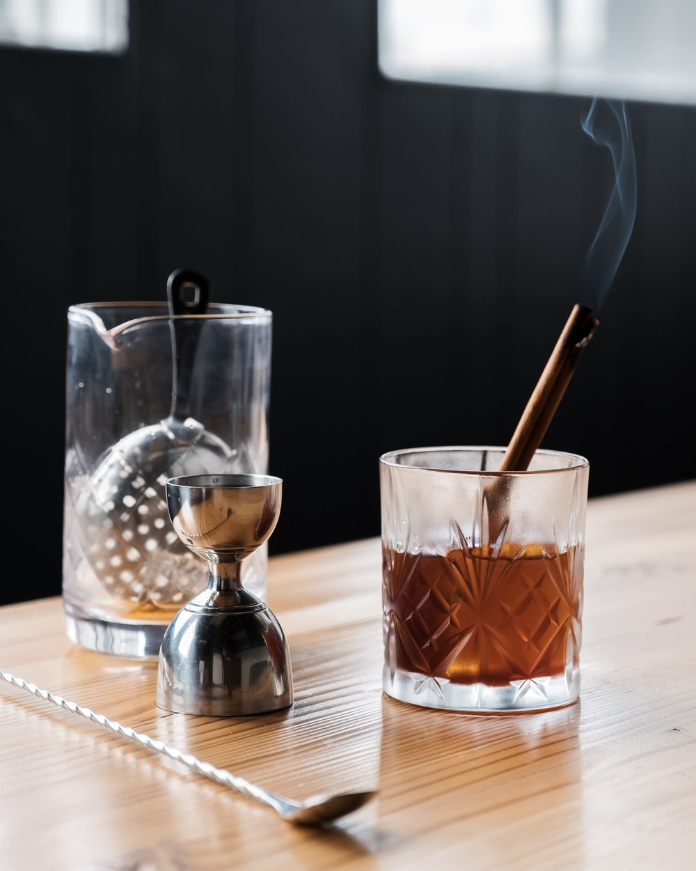 ingredients - 1 oz mezcal Espadin1 oz cold brew coffee1/2 oz *Allspice syrupGarnish with a burning cinnamon stick