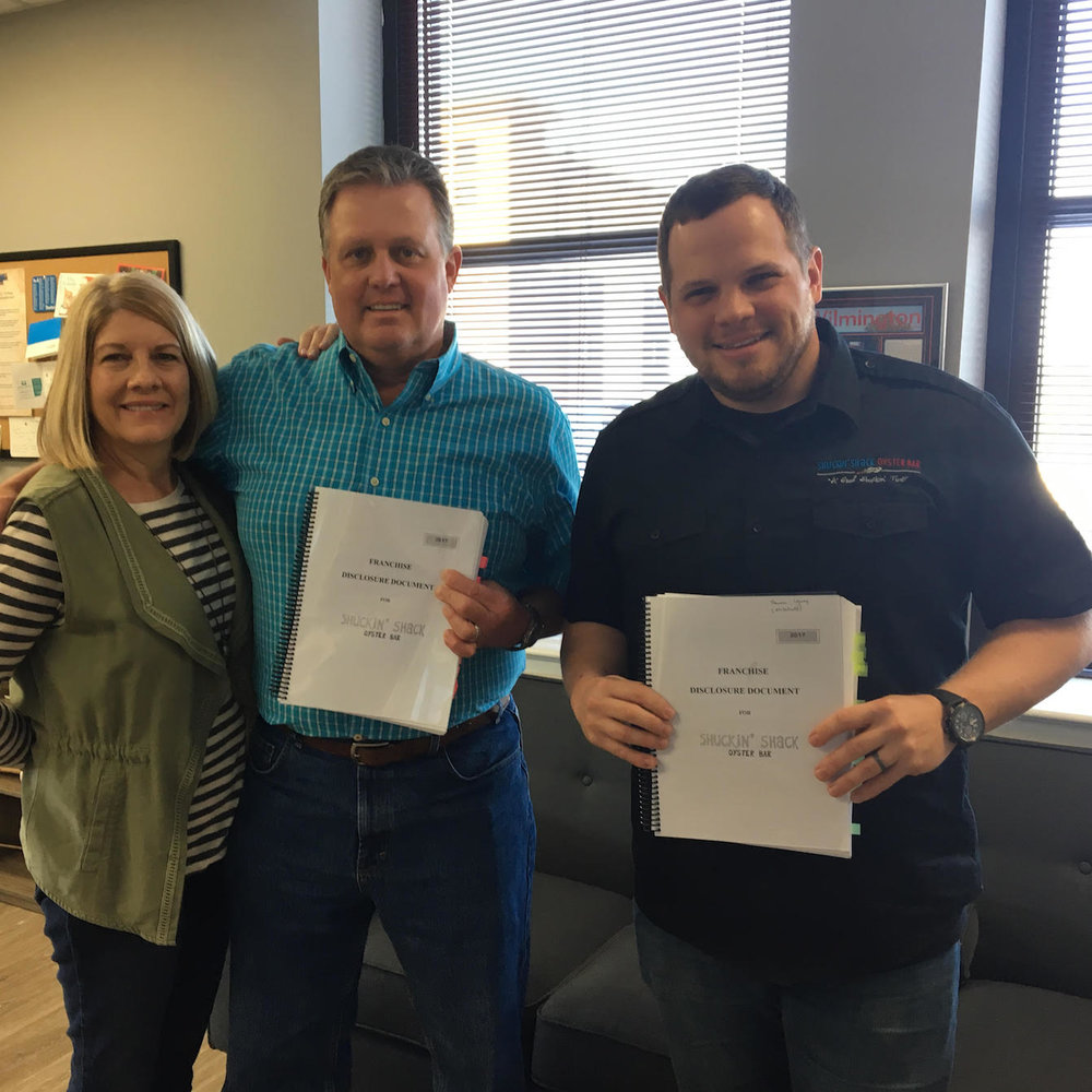 The Mitchell family from Cumming, GA (left) stand with Shuckin' Shack Franchising CEO, Jonathan Weathington, immediately after signing their franchise agreement yesterday!
