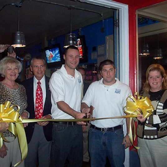 Sean Cook (in white on the left) and Matt Piccinin (in white on the right) cut the ribbon during the grand opening of the Carolina Beach Shuckin' Shack 11 years ago.