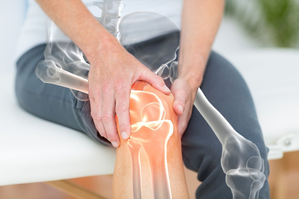 Mid section of man suffering with knee pain