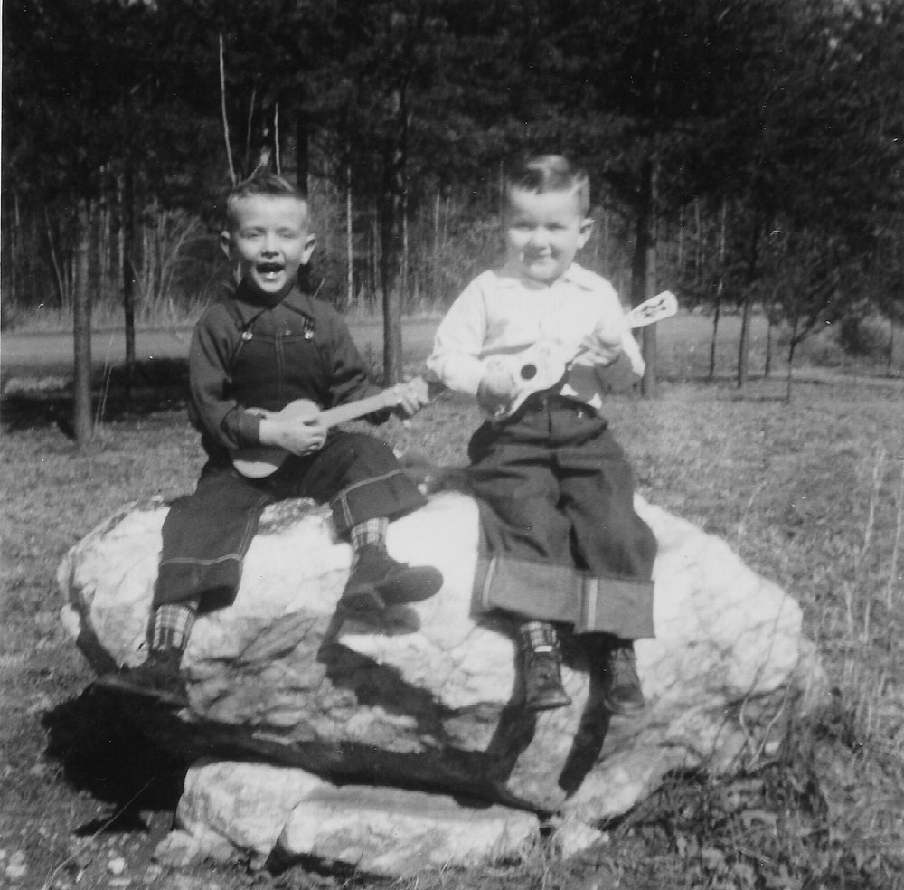 Tony and his brother Gary, pictured with tiny guitars, grew up playing music.