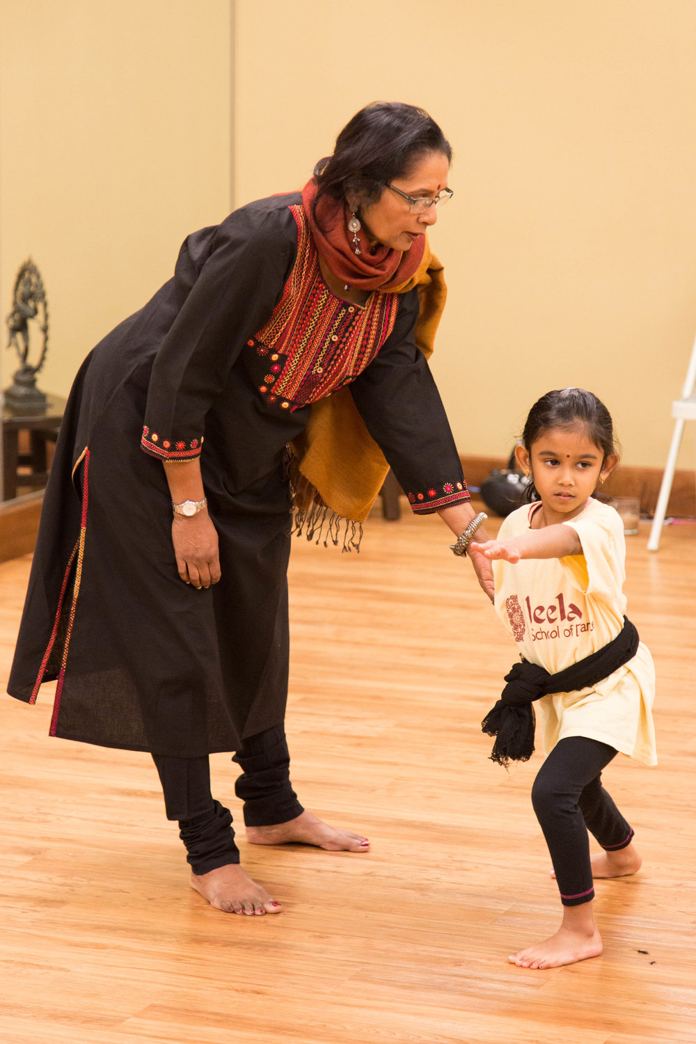 Asha Bala adjusts form of young student.