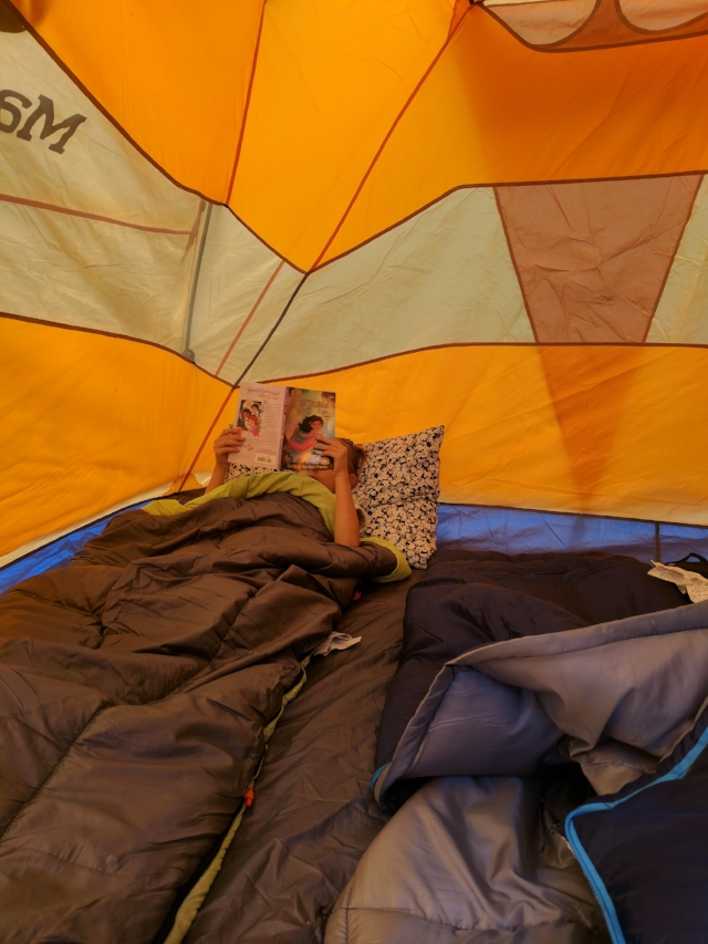 Lilly reading in their tent.