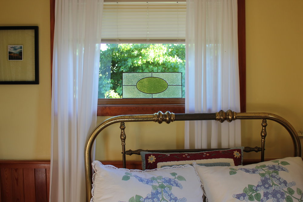 plum nelli iron bed and stain glass window in antique washington farm house.JPG