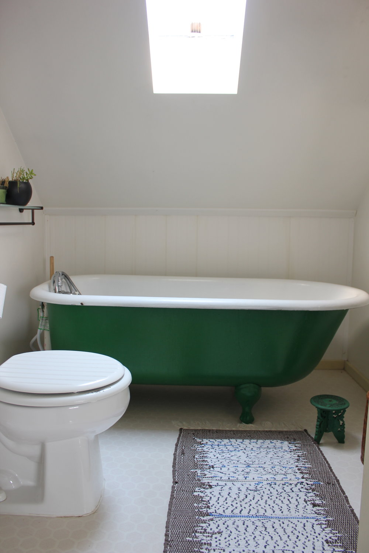 green clawfoot bathtub and handwoven rug at plum nelli farm chic home rental.JPG