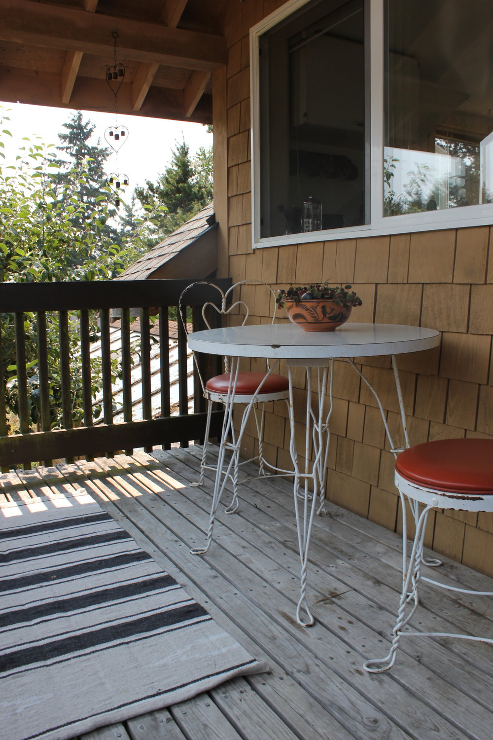 plum nelli apartment porch with vintage chairs plants and handwoven rug.JPG