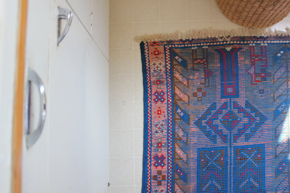 turkish rug and vintage cabinet details at plum nelli light filled apartment.JPG
