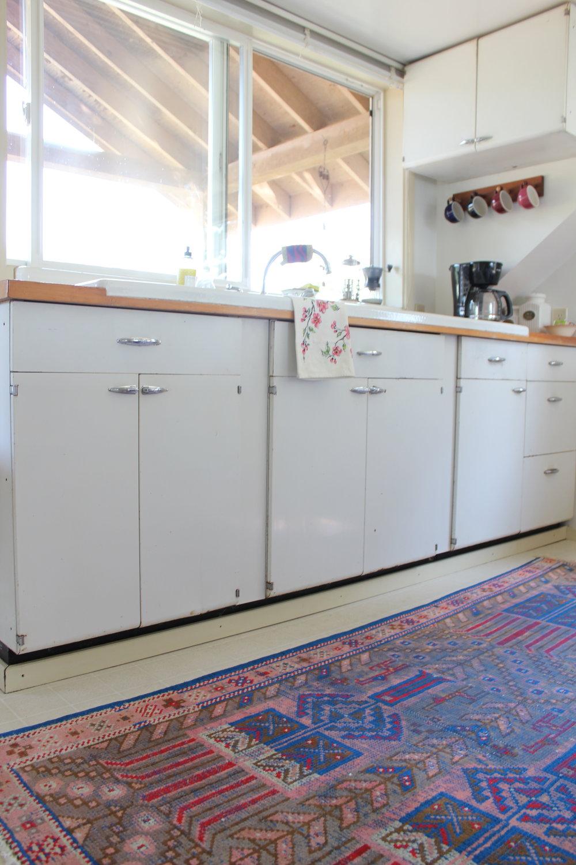 vintage cabinets and turkish rug in plum nelli washington farm home.JPG