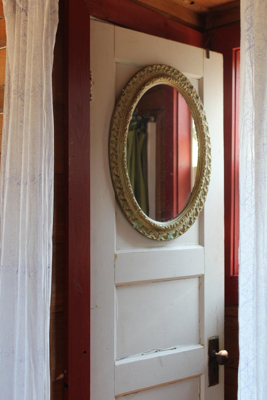 singing frog cabin vintage mirror on rustic bathroom door w red trim.JPG