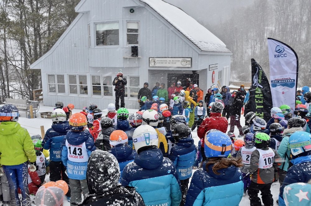 In heavy snow, Dave Steele explains the day's events to all the participants outside the Ski Runners lodge.