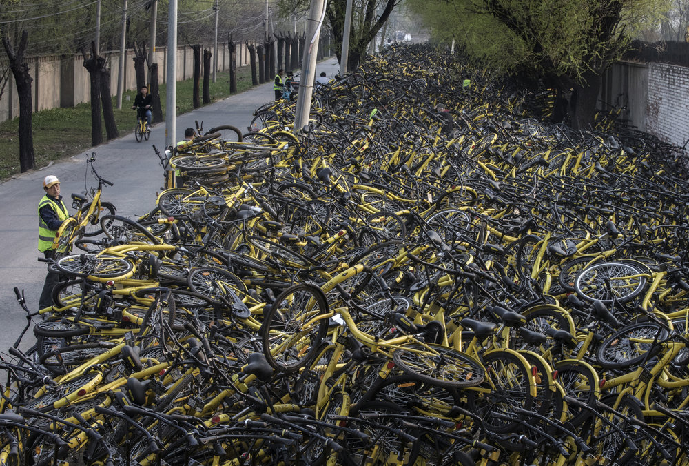 """Throughout China, there's thousands of bikes that are left abandoned in """"graveyards."""" 📸: Curbed ."""