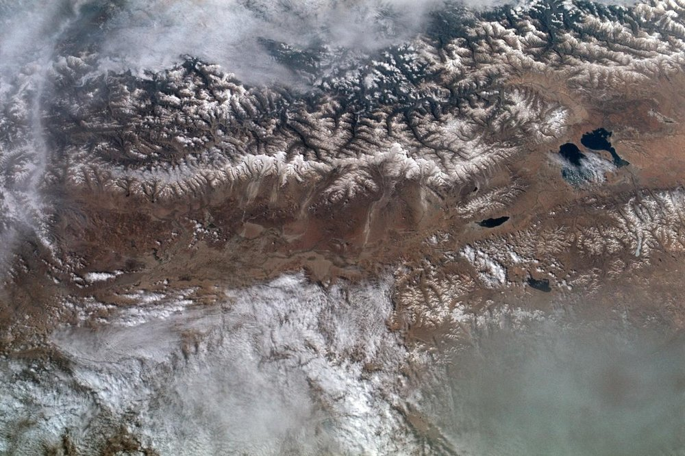 The Great Himalayan Mountain Range in Tibet, where mountains soar more than 20,000 feet tall and are always coated in a layer of snow. Laga Co and Kunggyu Co lakes can be seen in this 1973 photo, located just inside the Tibet. 📸:  NASA