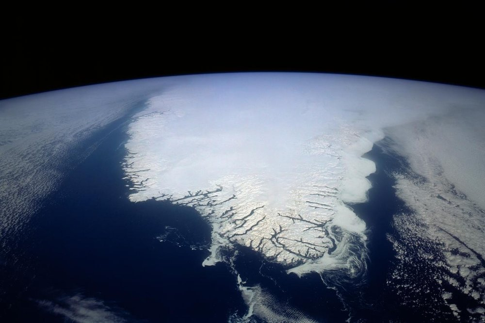 Greenland covered in snow, with indents along the coastline where settlements are located. The centre of the country is more than 10,000 feet thick and is filled with large ice rivers. 📸:  NASA
