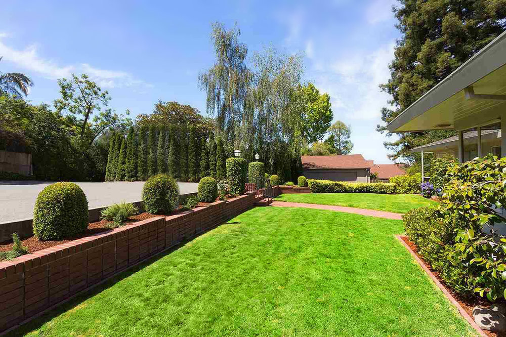 THE PRIVATE DRIVE LEADS TO A WIDE,LEVEL FRONT YARD. CROQUET, ANYONE?