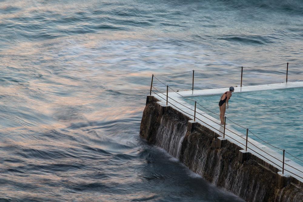 swimmer preparing to dive into ocean pool