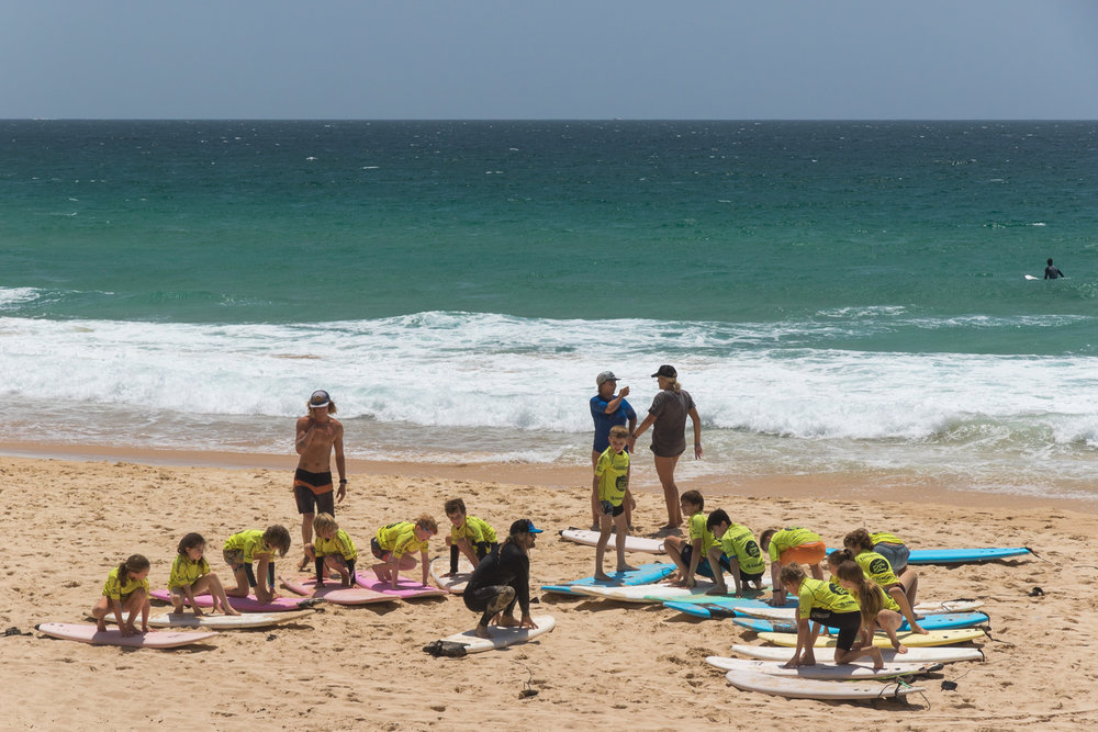 surf instructor teaching a group of beginner surfers in australia