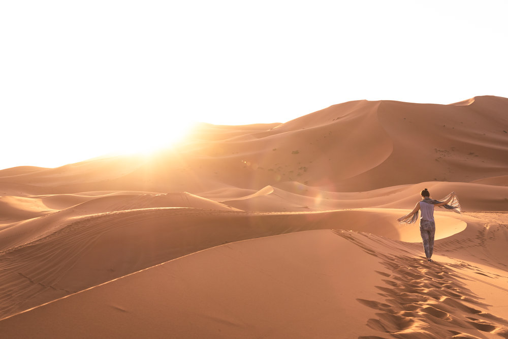 a female traveler taking in the golden light at sunrise in the sahara desert