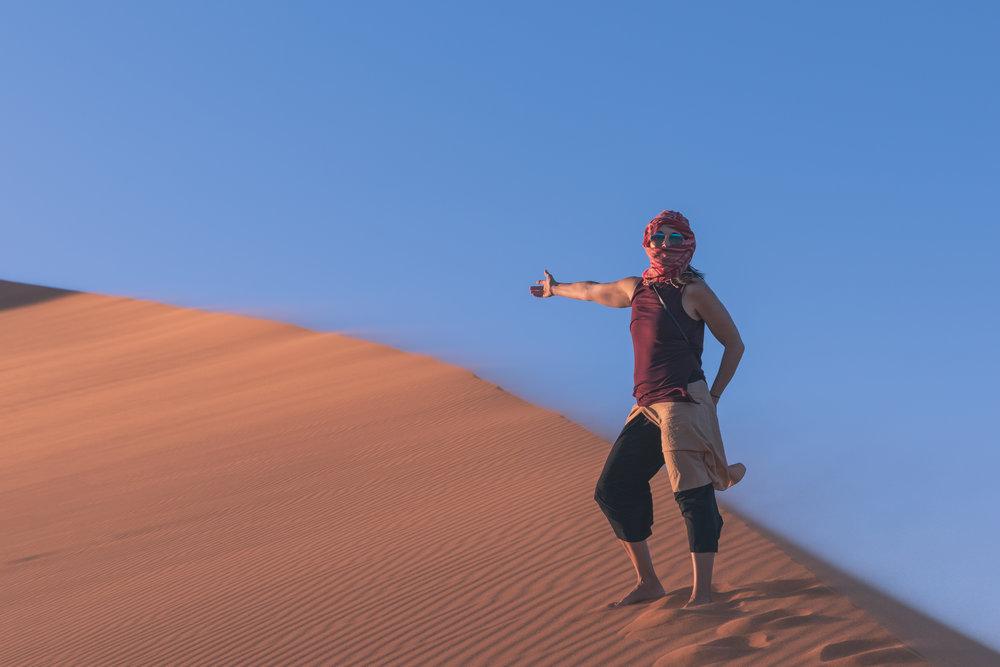 female traveler climbing sand dune in Morocco