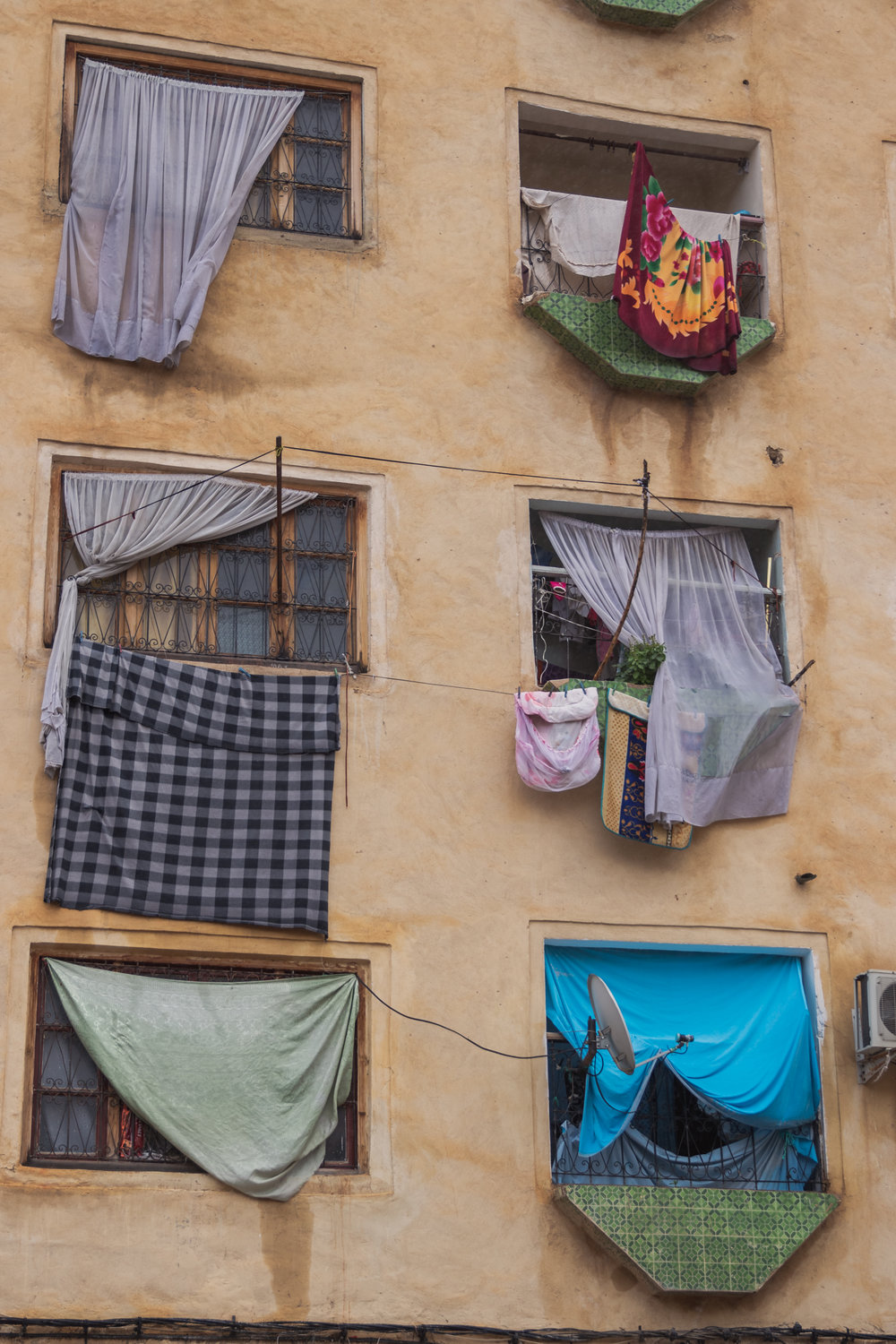 window drapes of different colours and patterns on an apartment building in Fez Morocco