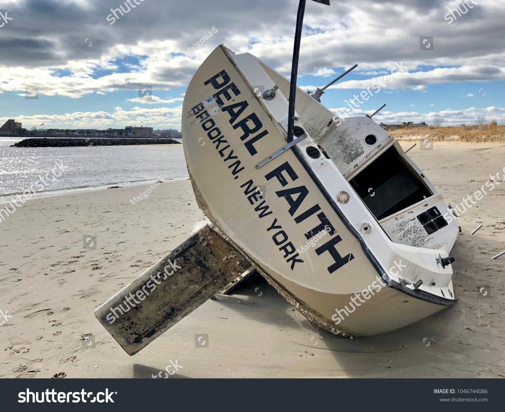 Overturned boat washed ashore by strong storm on Plumb Beach, Brooklyn, NY.