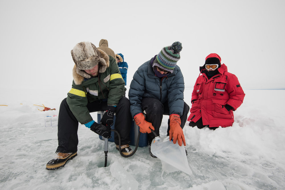 Zac Cooper, Shelly Carpenter and Jody Deming collecting seawater under the ice. Photo credit: A. Torstensson