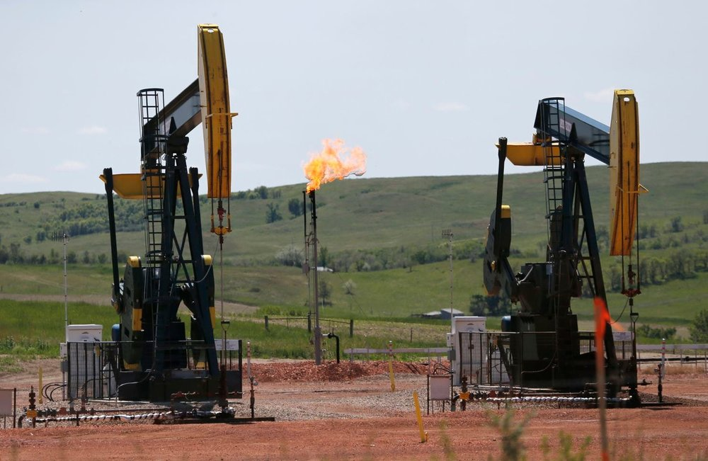 Natural gas burn off near oil pumps in Watford City, N.D. (Charles Rex Arbogast/AP)
