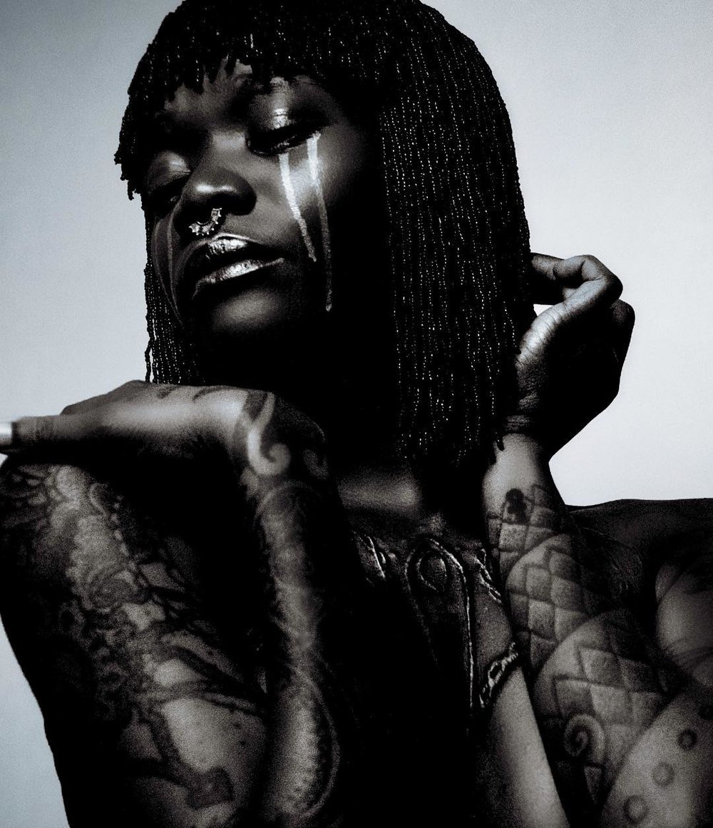 ABOUT MONIASSE - Adorned in body scarification and tattoos, Moniasse also known as Laurence Sessou, 'accidentally' began her modelling career in Mexico after being regularly stopped for pictures in the streets of Playa del Carmen. Since then she has worked with different designers, photographers such as Nick Knight, sculptor Marc Quinn and other creatives — often posing as their muse. In 2016, she featured in the television adaptation of Zadie Smith's novel N.W alongside Nikki Amuka-Bird and is the ambassador for Nubian Skin's Moroccan Nights lingerie line.From the Republic of Benin, Laurence grew up in the small town of Evereux, Normandy in France. In 2000, she moved to London and has been working as a Neuromuscular Therapist since graduating from the University of Westminster in 2007.She has travelled extensively across South East Asia, Latin America, USA, Europe and Africa and is fluent in French, English and Spanish. She enjoys African dancing and has previously worked as a professional dancer and performer for over ten years.Inspired by her own sisterhood of supportive and creative women, she launched her collective 'AZO-OUI-WA' in July 2017. Meaning 'get the work done' in Fon (Benin), AZO-OUI-WA celebrates and champions women through creative projects and events throughout the year.