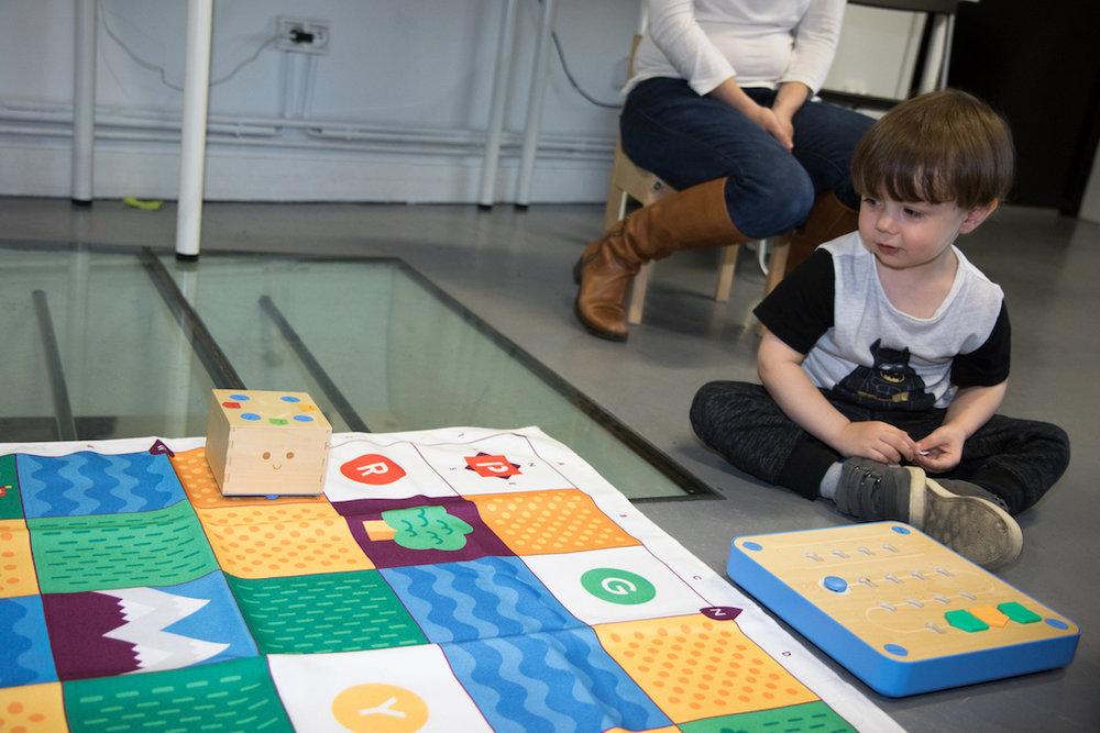 Un enfant de 3 ans observe son programme à l'oeuvre, d'un air plutôt satisfait.