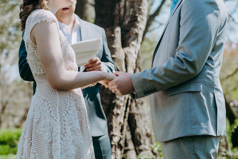 A couple holding hands and saying their vows during their wedding ceremony.