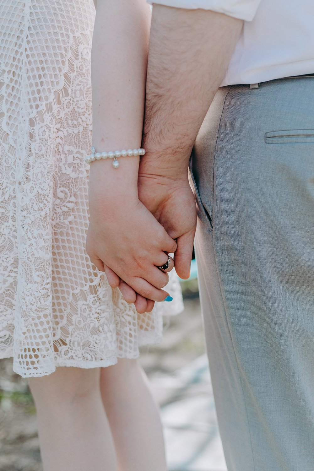 A close-up shot of the bride and groom holding hands.