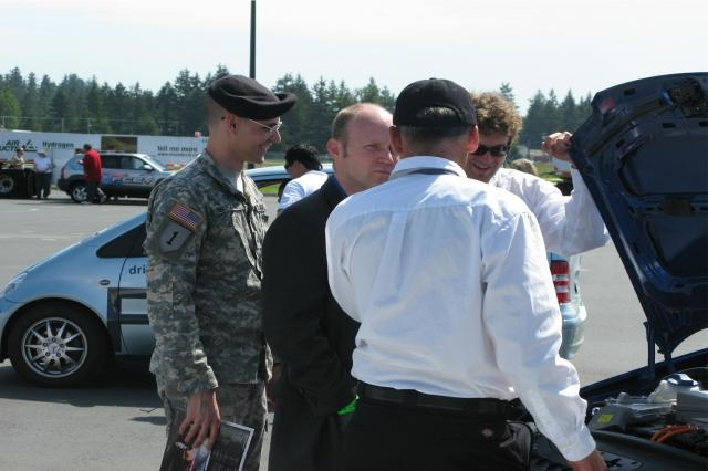 JOINT BASE LEWIS-MCCHORD SUSTAINABILITY PROGRAM WA State Representative Zachary Hudgins is shown the engine of a hydrogen fuel cell vehicle during the June 2009 West Coast Hydrogen Road Tour. The tour (from California to British Columbia) stopped at JBLM to encourage hands-on education. 50 people including Soldiers, family members, retirees, and government employees test drove 12 hydrogen fuel cell vehicles and talked with tour experts.  (Photo Credit: Karli Steffy) VIEW ORIGINAL
