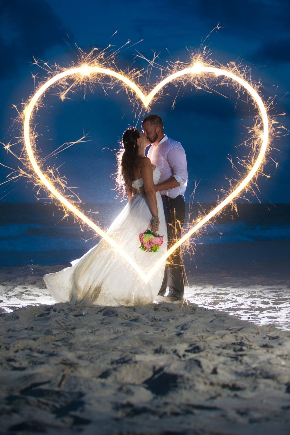 Long exposure shot of bride and groom kissing on Myrtle Beach surrounded by sparkler heart