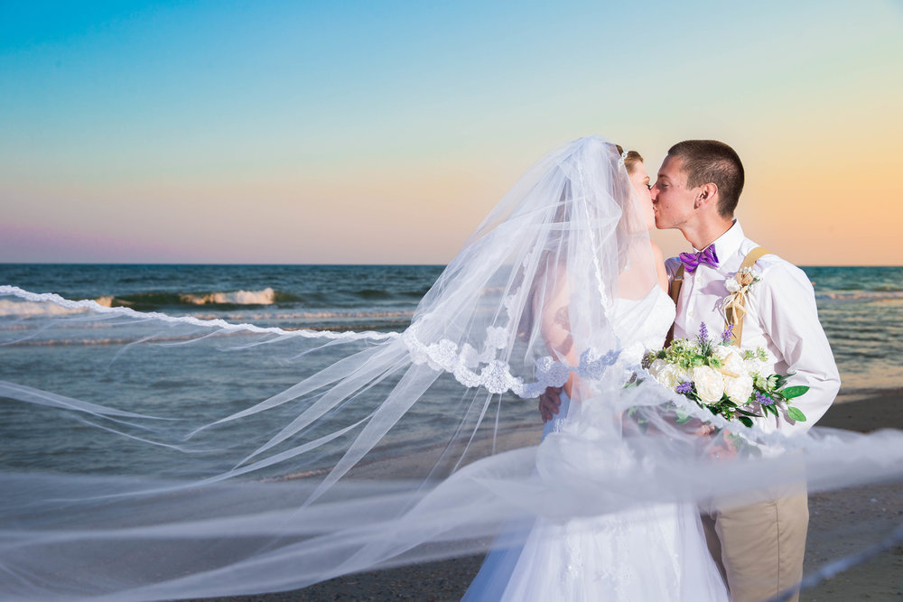 Couple kissing on Myrtle Beach in their wedding attire.