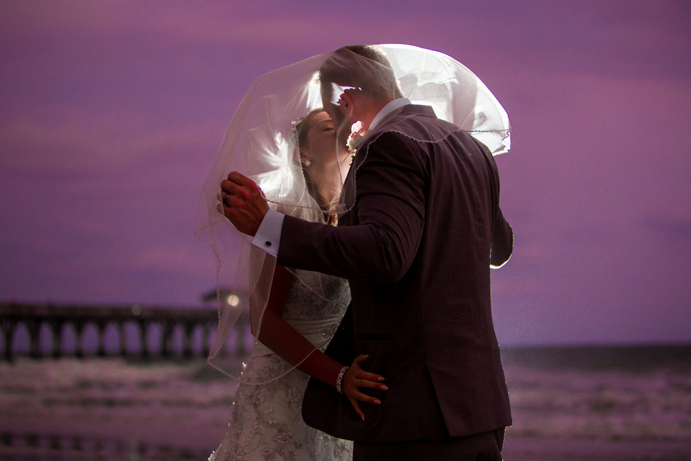 Newlyweds kissing at twilight on the beautiful Myrtle Beach shore