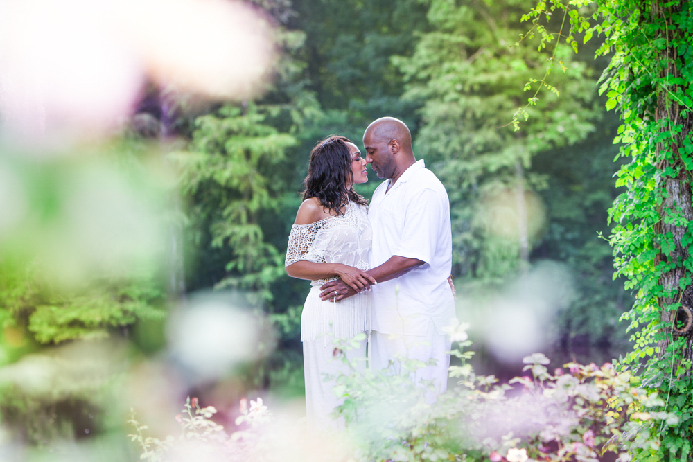 Husband and wife embrace in a natural setting surrounded by greenery.