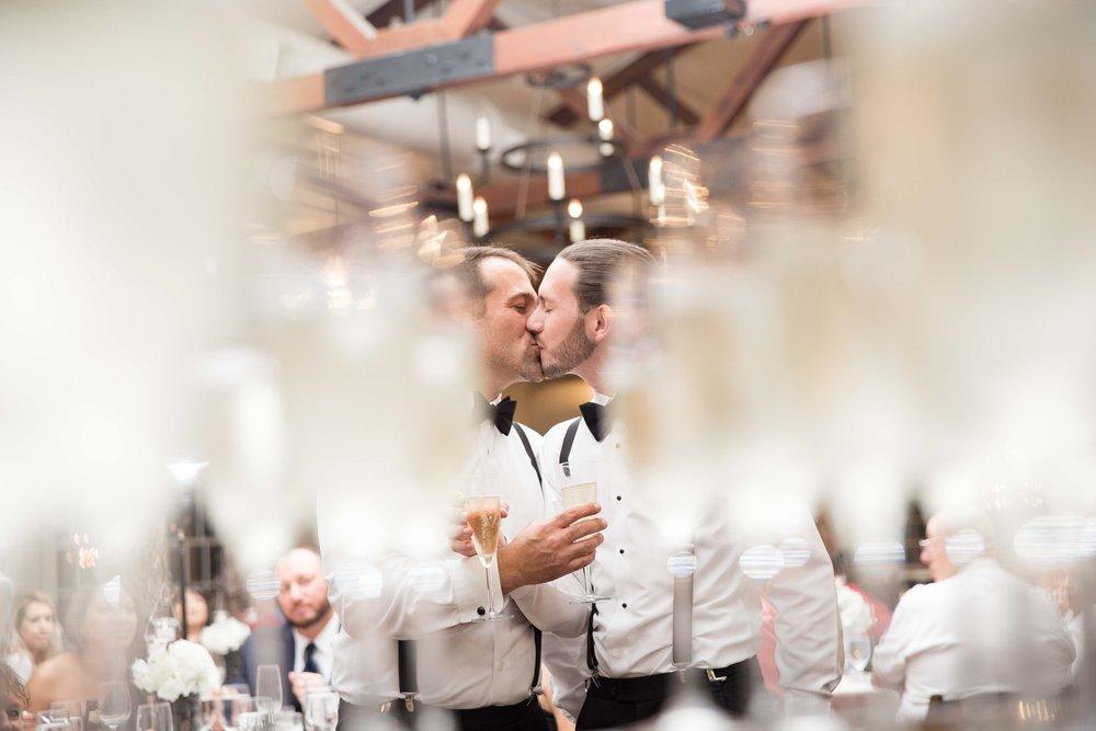 Groom kisses groom during champagne celebration after ceremony