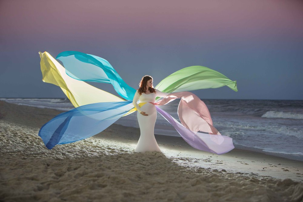 Maternity session on the beach with colorful ribbons flowing from dress.