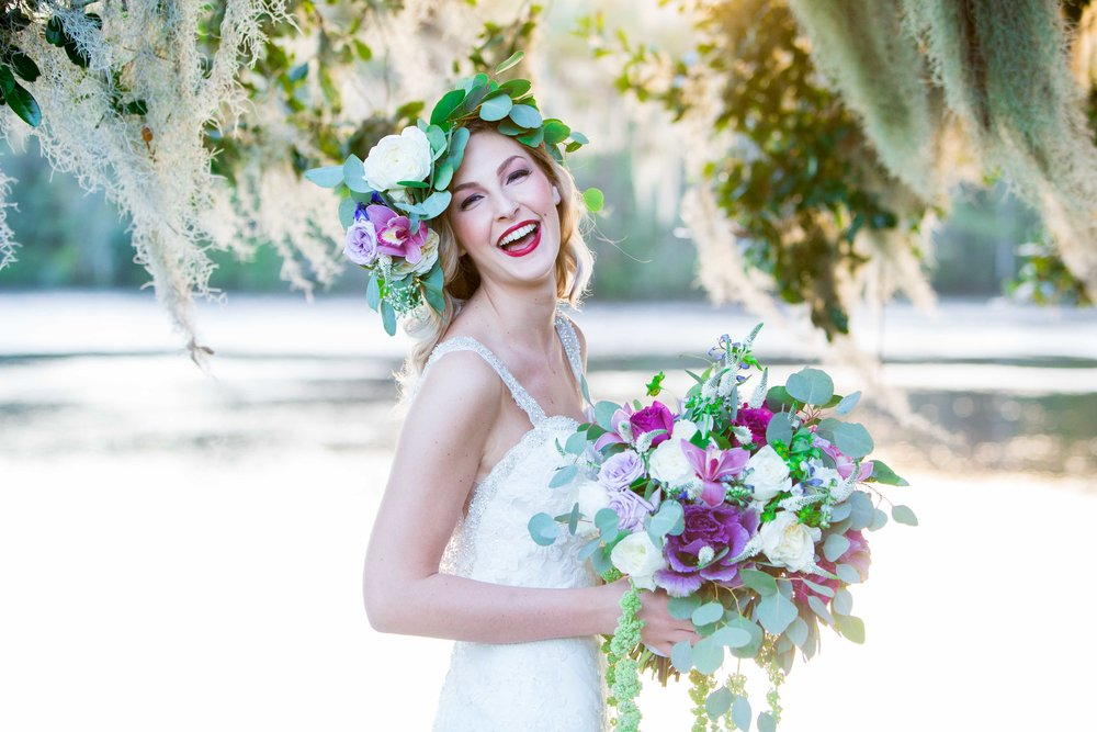 Bride smiles while looking into the camera holding a lush bouquet.