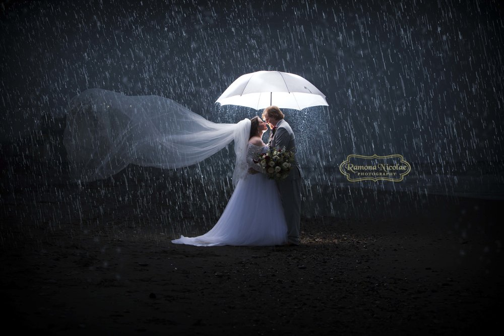 bride and groom embracing under lit umbrella in the rain in myrtle beach by ramona nicolae photogrpahy.jpg