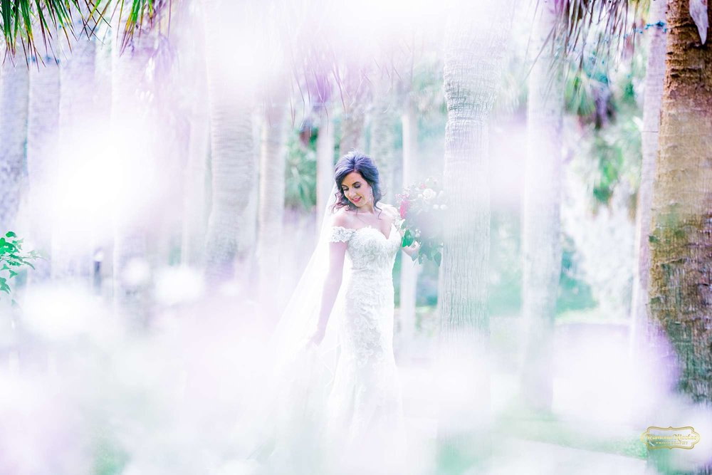 bride at brookgreen gardens with white flowers in foreground holding red flowers bouqet by ramona nicolae photography best myrtle beach wedding photographer-2.jpg