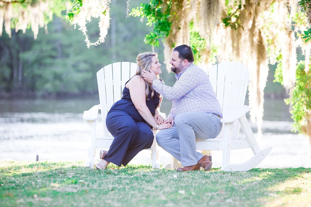 kissing on white rocking chairs for engagement shoot at wachesaw plantation.jpg