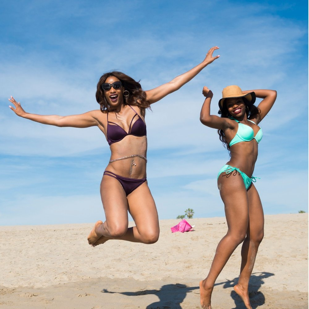 two-women-jumping-in-air-at-venice-beach-california-picture-id475842926.jpg