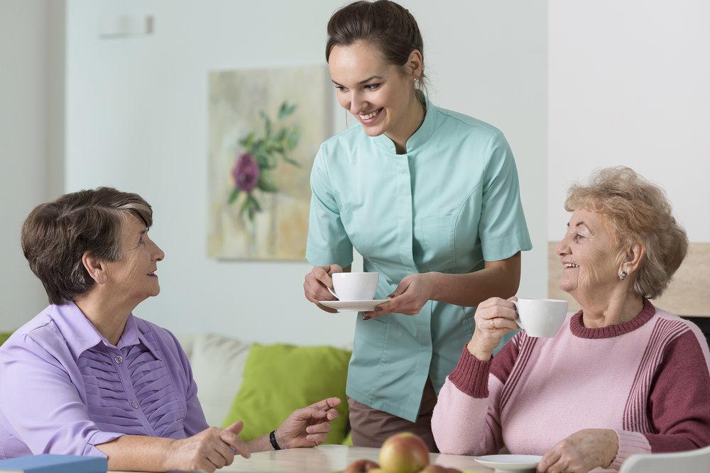 Staff helping seniors with tea