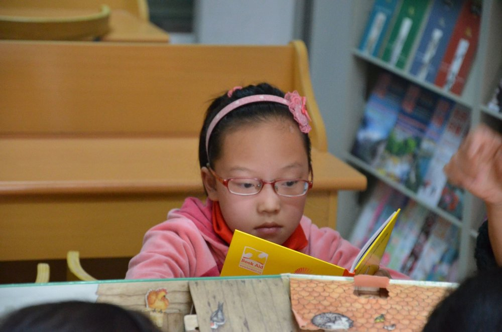 This young lady is reading the book I donated to the library in Lang Xia Primary School.