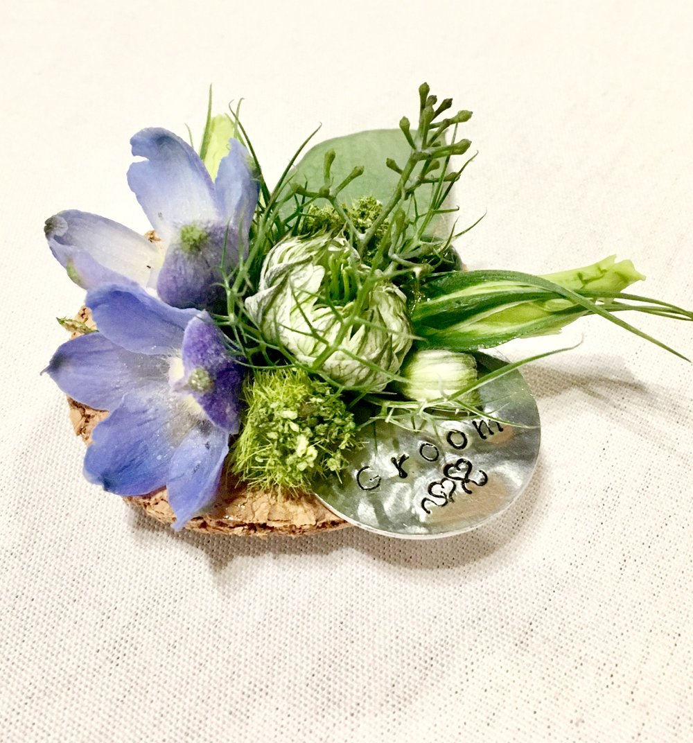 """Boutonniere with personalized """"Groom"""" bauble, designed on natural cork with delphinium, nigella, moss, eucalyptus seeds and lisianthus buds."""